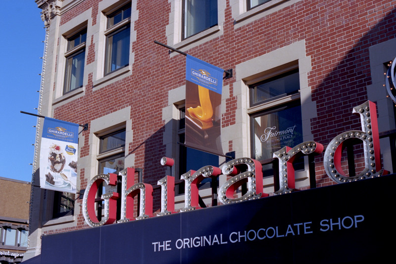 The large red Original Chocolate Shop sign stands above the Chocolate Cafe at Ghirardelli Square. Ghirardelli banners are placed above the marquee, and the background for all is the red brick facade of the building.