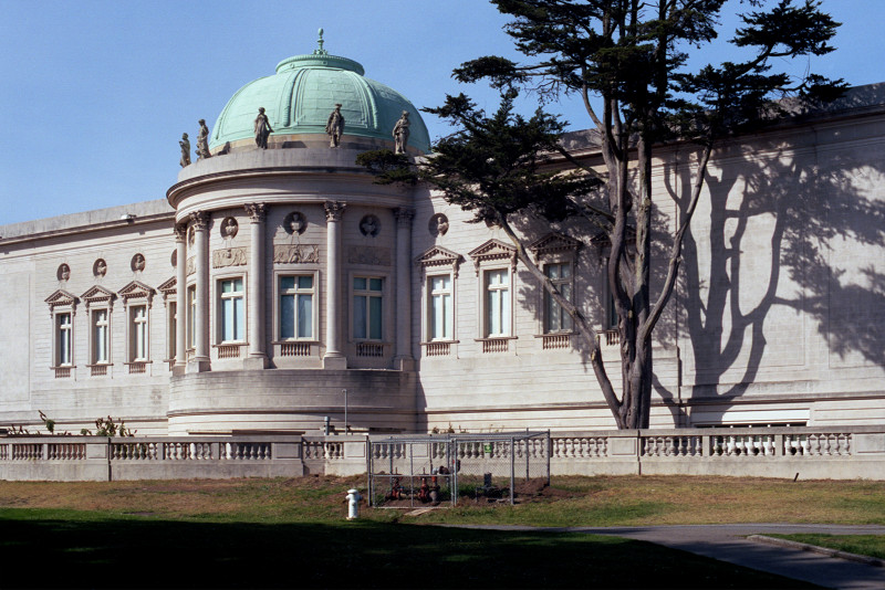 This photo shows the full length of the west elevation of the California Palace of the Legion of Honor, a view not to be missed. A large cypress tree stands next to the Rotunda. There are windows in the wall on both sides of the Rotunda.