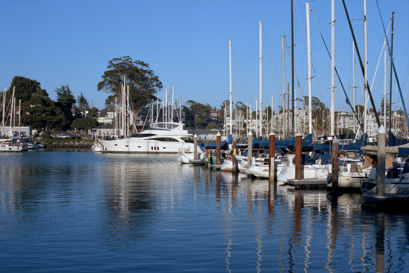 A large motor yacht at center of the picture, with smaller craft - mostly sailboats - docked closer in to the camera, on the right of the picture. Some buildings shown on the opposite shore of the Santa Cruz Yacht Harbor.