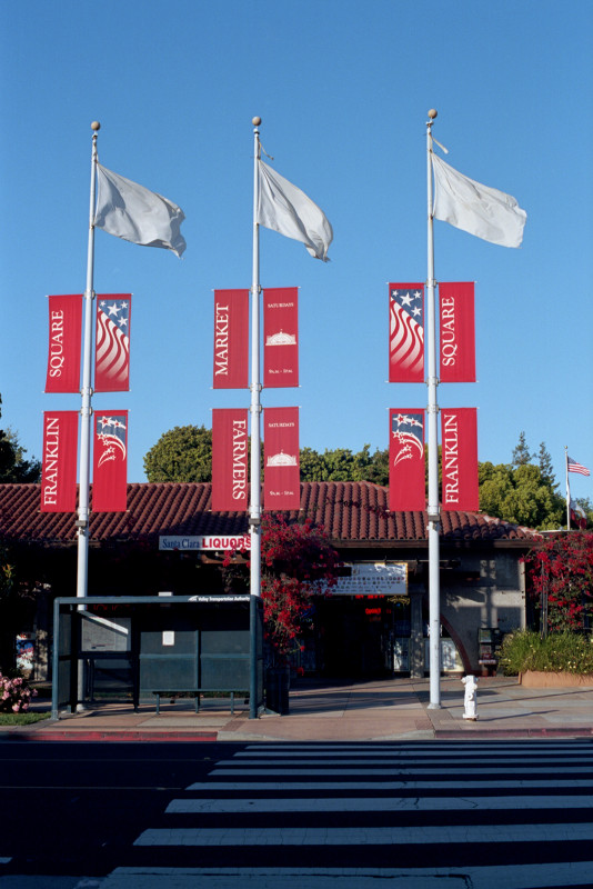 Three white flagpoles raise white flags and red scrolls announcing Franklin Plaza in Santa Clara, the center of the municipality. There are a number of businesses here in this pleasant environment.